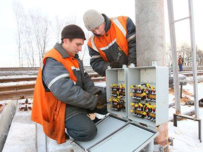 Электромеханик Денис Астапович и электромонтер Дмитрий Летун подключают устройства ЭЦ нового стрелочного перевода