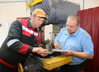 Мастер Алексей Литвин (справа) с фрезеровщиком Игорем Цветковым обсуждают новую разработку - приспособление для фрезеровки валика подъемника