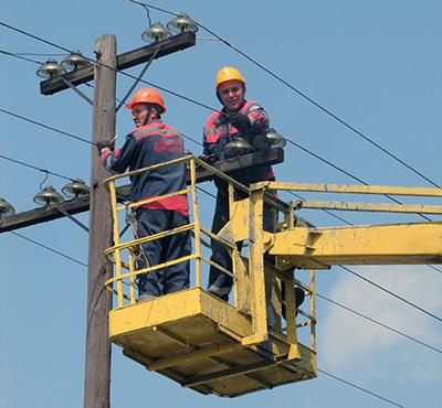 Работники дистанции снимают провода с траверсы на старой опоре линии электропередачи