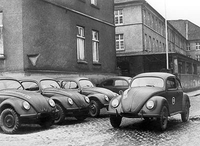 In 1945 the first Volkswagens made in West Germany, at Bonneberg near Kerford, are parked in the factory's courtyard. The Beetle owes its existence to Adolf HITLER's will to equip the IIIrd Reich with a popular car. It became commercialized only in the post-war period and is a symbol of those years. En 1945, les premières Volkswagen fabriquées en Allemagne de l'Ouest, à Bonneberg, près de Kerford sont stationnées dans la cour de l'usine. La Coccinelle doit son existence à la volonté d'Adolf HITLER de doter le IIIe Reich d'une voiture populaire. Elle n'est commercialisée qu'après-guerre et constitue un symbole de ces années-là.