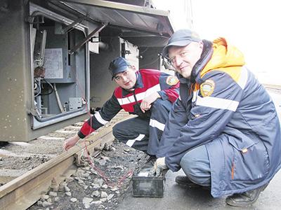Слесари-электрики Вячеслав Кустовский (справа) и Владислав Володькин осуществляют проверку сопротивления изоляции высоковольтной магистрали в вагоне