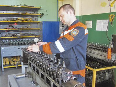 Слесарь по ремонту топливной аппаратуры Александрь Поливода проверяет размер подъема нагнетательного клапана ТНВД на кантователе