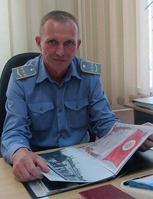Григорий Галух показывает книгу истории станции