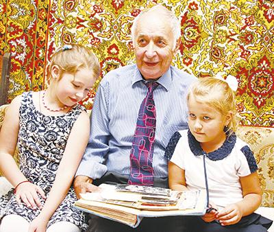 Внучки Марта и Влада с интересом слушают рассказы Федора Серафимовича и рассматривают фотографии из семейного альбома