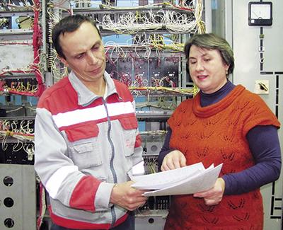 Электромеханик Андрей Наумченко и инженер отдела по ведению техдокументации Евгения Шатиленя за сверкой схем подключения устройств СЦБ